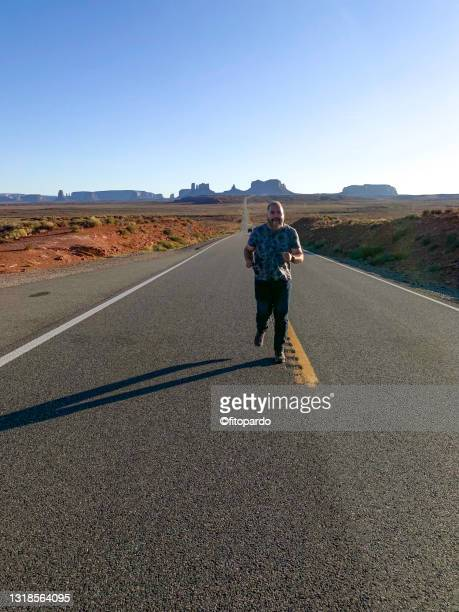 man running in the middle of the road close to monument valley - fitopardo stock pictures, royalty-free photos & images