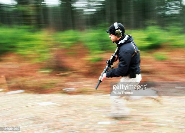 Man running in the woods with a rifle.