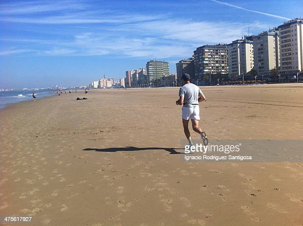 A man running in Victory's Beach Cádiz Spain There is no better place in the world to practice your favorite sport