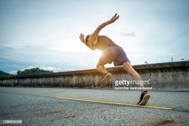 man running jogging on bridge road. health activities, exercise by runner. - marathon stock pictures, royalty-free photos & images