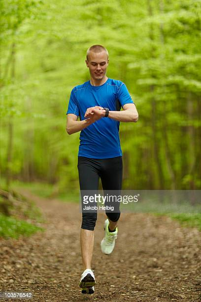 Man running, looking at sports watch