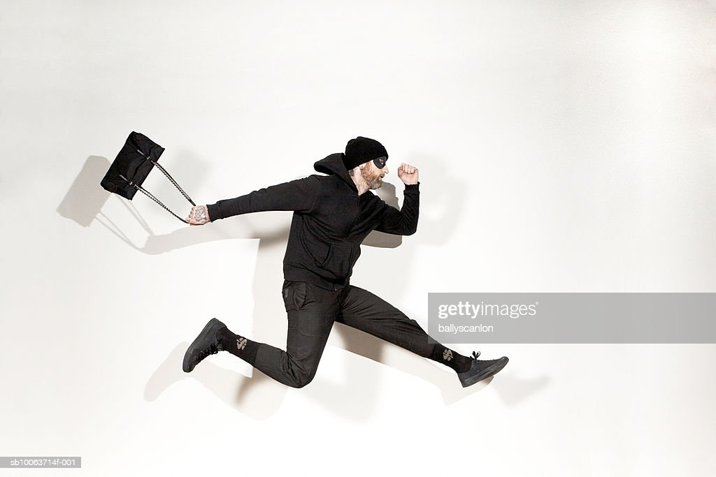 Man running mid-air with handbag, side view : Stock Photo