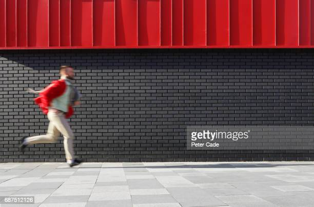 man running next to black and red building - urgency stock pictures, royalty-free photos & images