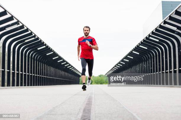 man running on a bridge - forward athlete stock pictures, royalty-free photos & images