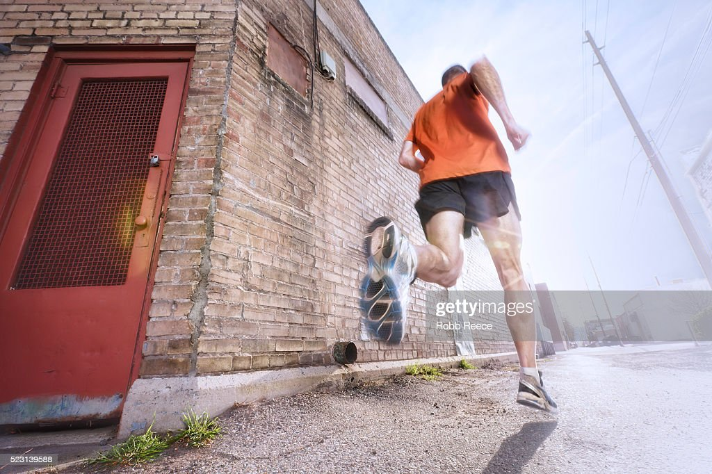 A man running on a city street for fitness : Stock Photo