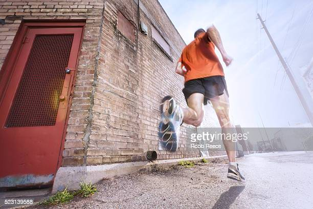 a man running on a city street for fitness - robb reece stock pictures, royalty-free photos & images