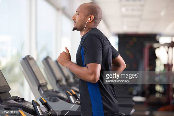 Man running on a treadmill in health club.