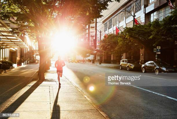 Man running on empty city street during early morning workout