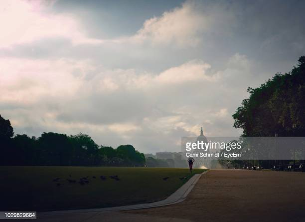 man running on field against cloudy sky - washington dc photos et images de collection