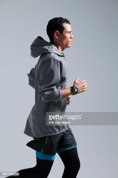 Man running on grey background wearing workout apparel