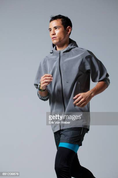man running on grey background wearing workout apparel - パーカー服 ストックフォトと画像