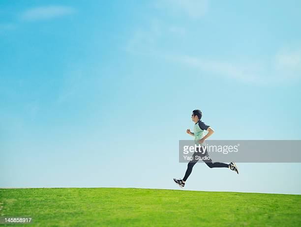 man running on lawn - jogging stock pictures, royalty-free photos & images