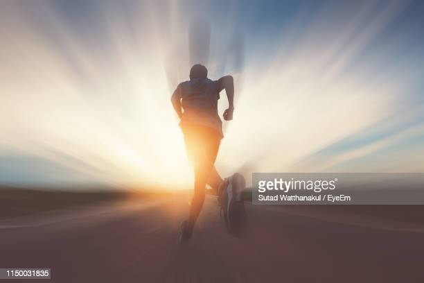 man running on road against sky during sunset - forward athlete stock pictures, royalty-free photos & images