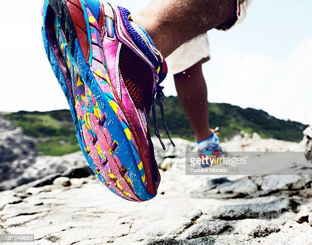 man running on rocks, rearview