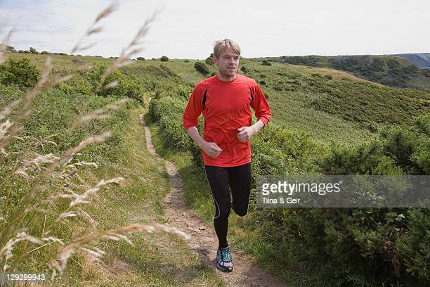 man running on rural path - gower peninsula stock photos and pictures