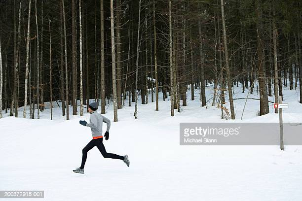 Man running on snow, side view