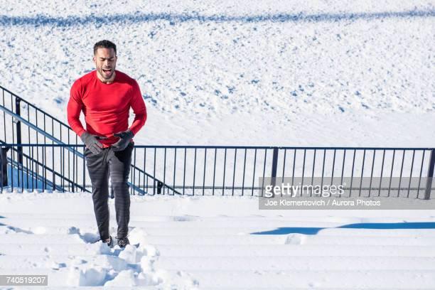 Man running on stadium bench in snow