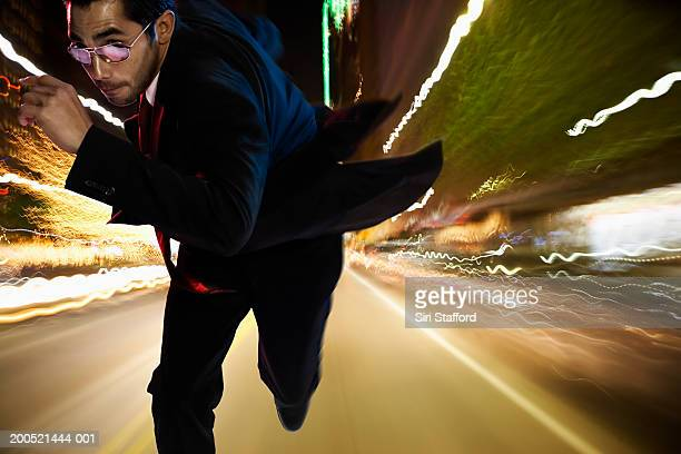 Man running on street at night (Digital Composite)