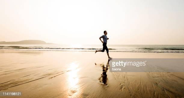 man running on the beach at sunset - adulto de idade mediana imagens e fotografias de stock
