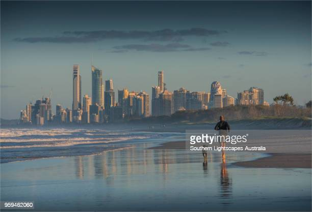man running on the beach with his dog at the spit, gold coast, queensland. - gold coast stock pictures, royalty-free photos & images