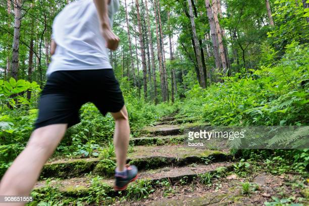 man running on the steps of forest - center athlete stock pictures, royalty-free photos & images