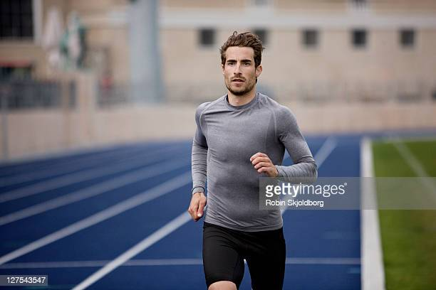 man running on track - athleticism stock pictures, royalty-free photos & images