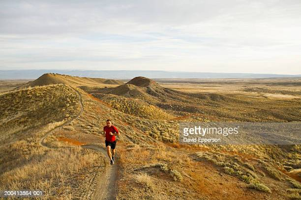 man running on trail in hills - fruita colorado stock pictures, royalty-free photos & images