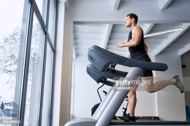man running on treadmill at gym - treadmill stock pictures, royalty-free photos & images