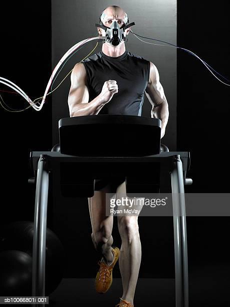 Man running on treadmill, wearing oxygen mask, portrait