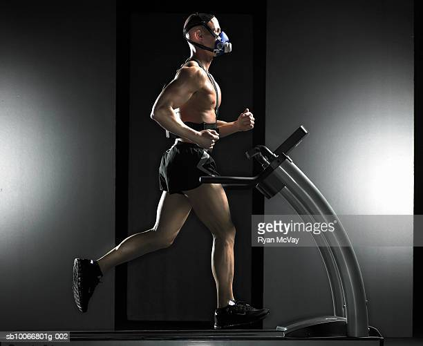 Man running on treadmill, wearing oxygen mask, side view