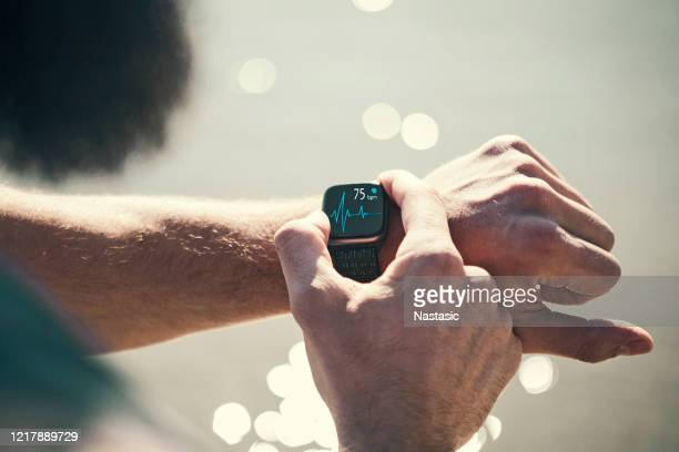man running outdoors running checking smart watch taking a break - wearable computer stock pictures, royalty-free photos & images