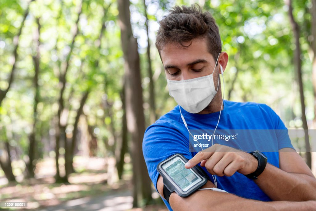 Man running outdoors wearing a facemask and using an arm band for his cell phone : Stock Photo