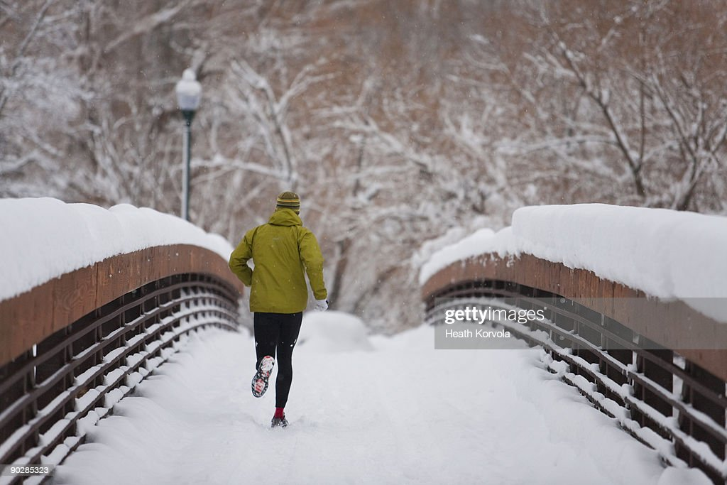 Man running over snow covered bridge in small town : Stock Photo