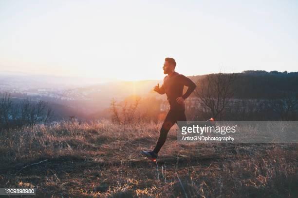 mann läuft bei sonnenuntergang über die stadt - joggen stock-fotos und bilder