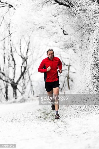 Man running through woods in winter, Wenlock Edge, Shropshire, England, UK