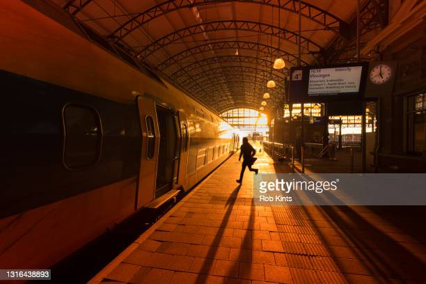 man running to catch a train on den haag hollands spoor train station - train vehicle stock pictures, royalty-free photos & images