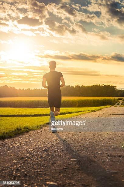 Man running towards sunset