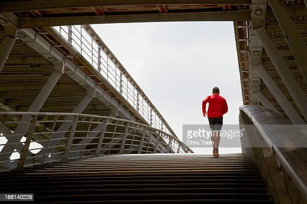 man running up a bridge