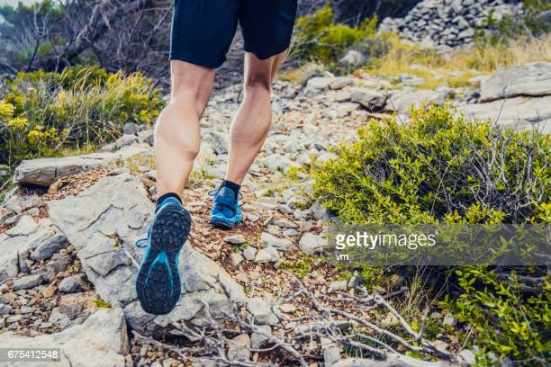 man running up a rocky hill - cross country running stock pictures, royalty-free photos & images