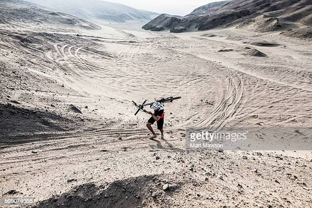 A man running up a sand dune holding his bike