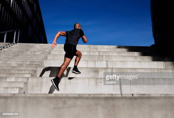 man running up outdoor stairs - steps stock pictures, royalty-free photos & images