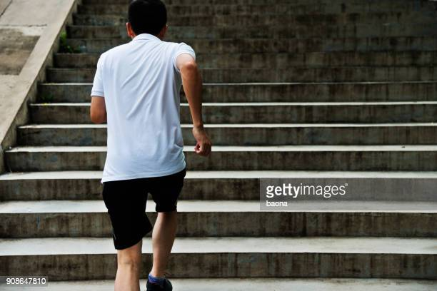 man running up outdoor stairs - center athlete stock photos and pictures