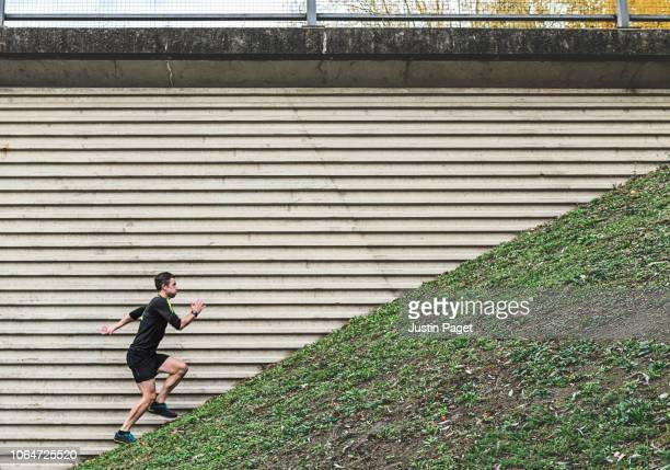 man running up steep hill - steep stock photos and pictures