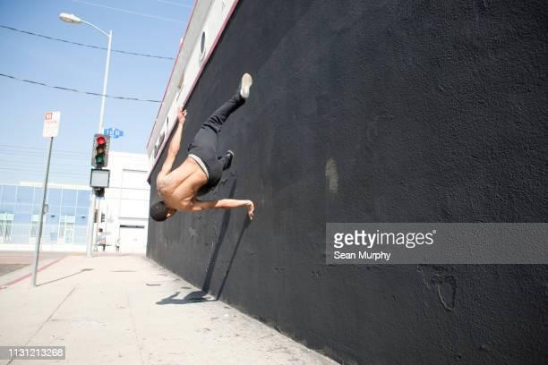 man running up wall, demonstrating parkour - le parkour stock-fotos und bilder