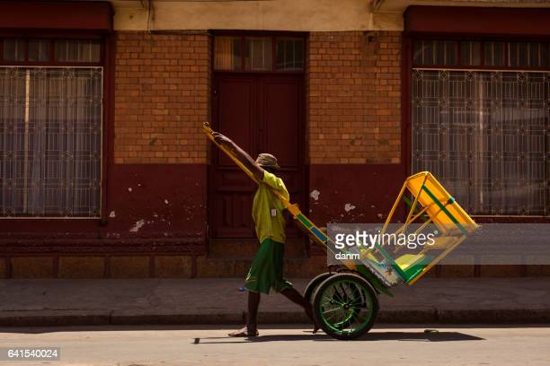 man running with a rickshaw in a full day in madagascar, africa. - antananarivo stock photos and pictures