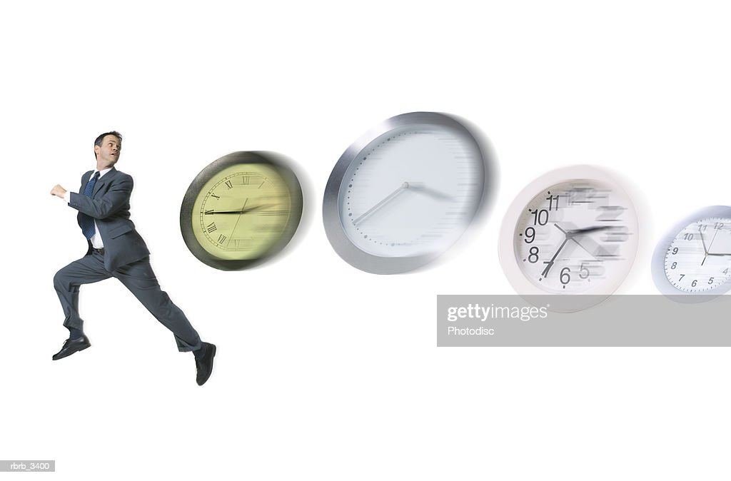 Man running with clocks chasing him : Foto de stock