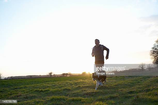 Man running with dog in countryside.