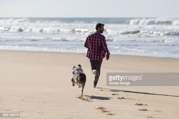 Man running with dog on beach