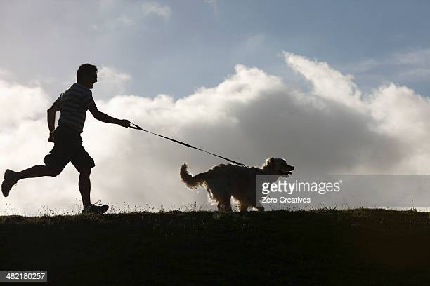 man running with dog on lead - guide dog photos et images de collection
