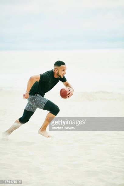 man running with football during game on beach with friends - rush american football stock pictures, royalty-free photos & images